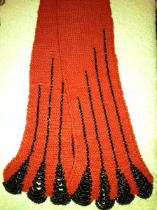 Red hand knitted scarf with black beadwork.